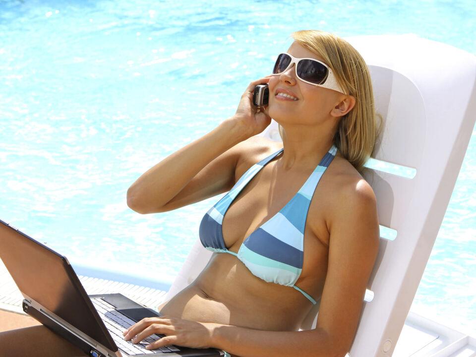 urlaub, internet, online-shopping, shopping, einkaufen Junge Frau mit Handy und Laptop am Pool (Modellfreigabe)