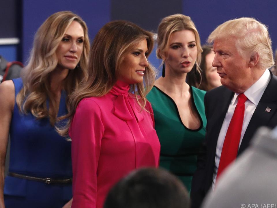 Melania Trump (in Rot) steht hinter ihrem Mann