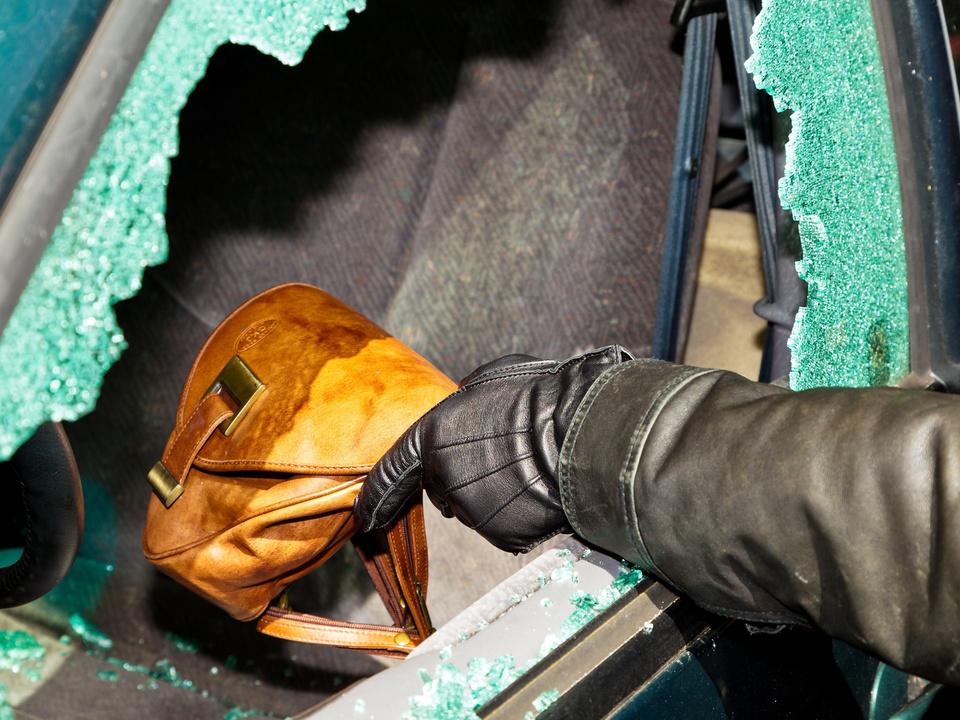 autoknacker scheibe einbrecher Ein Dieb entwendet eine Handtasche aus Auto