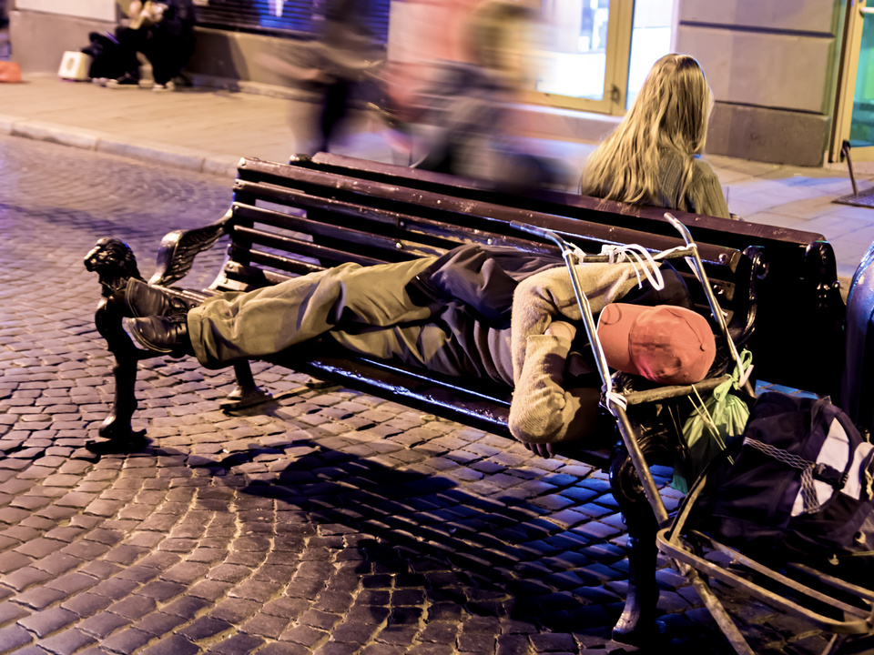 obdachlos armut A homeless man sleeping on a bench at night in the city