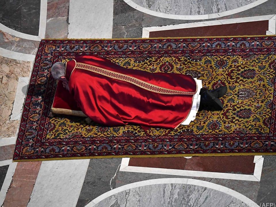 Papst Franziskus betet am Fuß des Kreuzes
