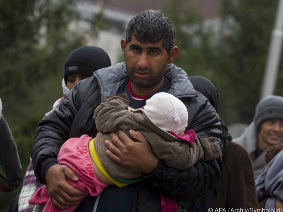 Ein Flüchtling hält sein Kind im Arm