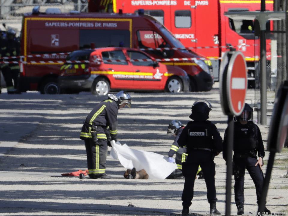 Feuerwehrleute decken den toten Täter