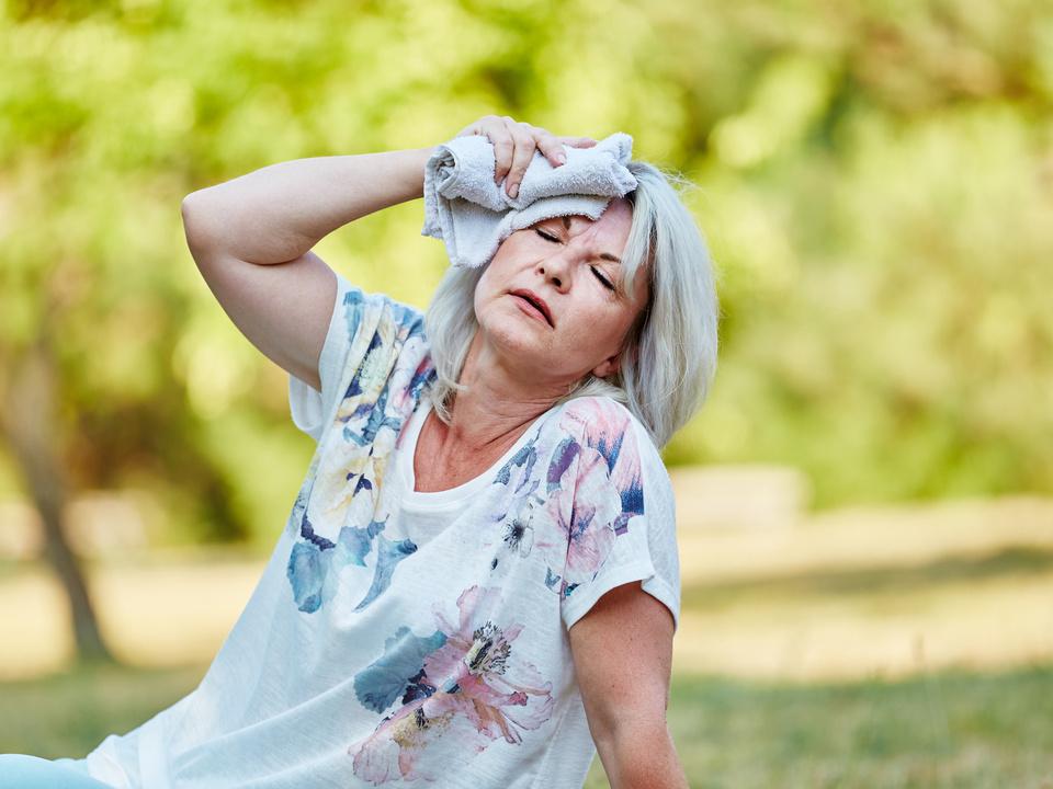 Hitze Senioren Alte Frau hlt feuchtes Tuch an die Stirn