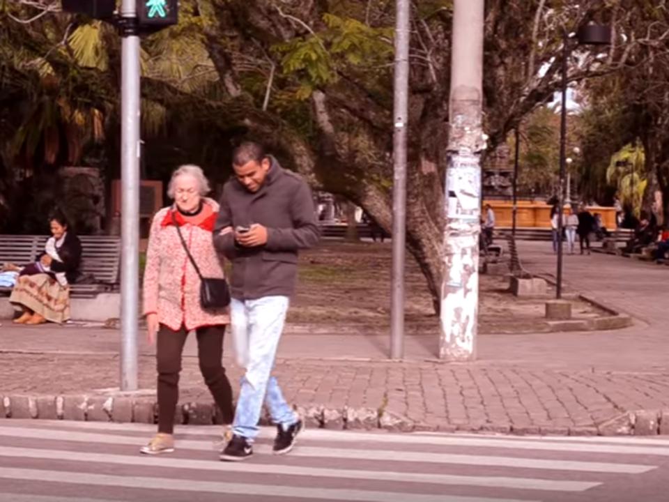 Oma begleitet Smartphone Nutzer über die Straße