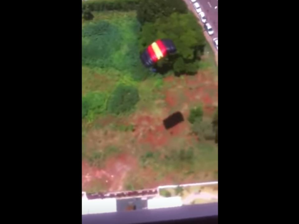 Mann springt mit Fallschirm von Balkon