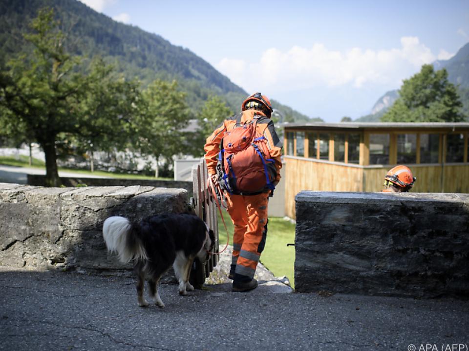 Einsatzkräfte suchen mit Hunden nach den Vermissten