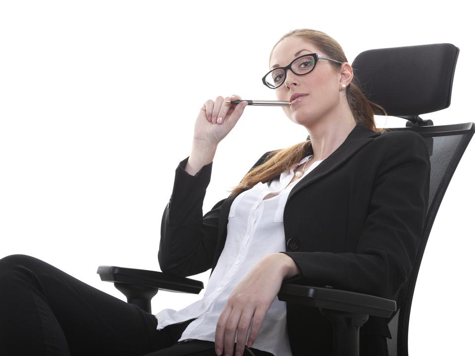 Frau Chef Business Managerin im Chefsessel mit Kugelschreiber im Mund