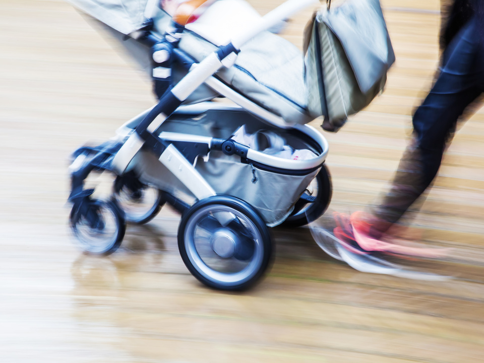 Mutter mit Kinderwagen in der Stadt in Bewegungsunschärfe