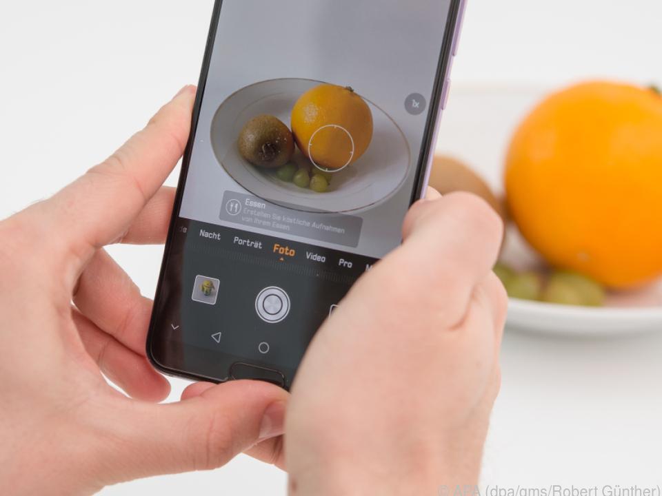 Die KI erkennt die Orange und richtet die Kamera für ein Food-Foto ein