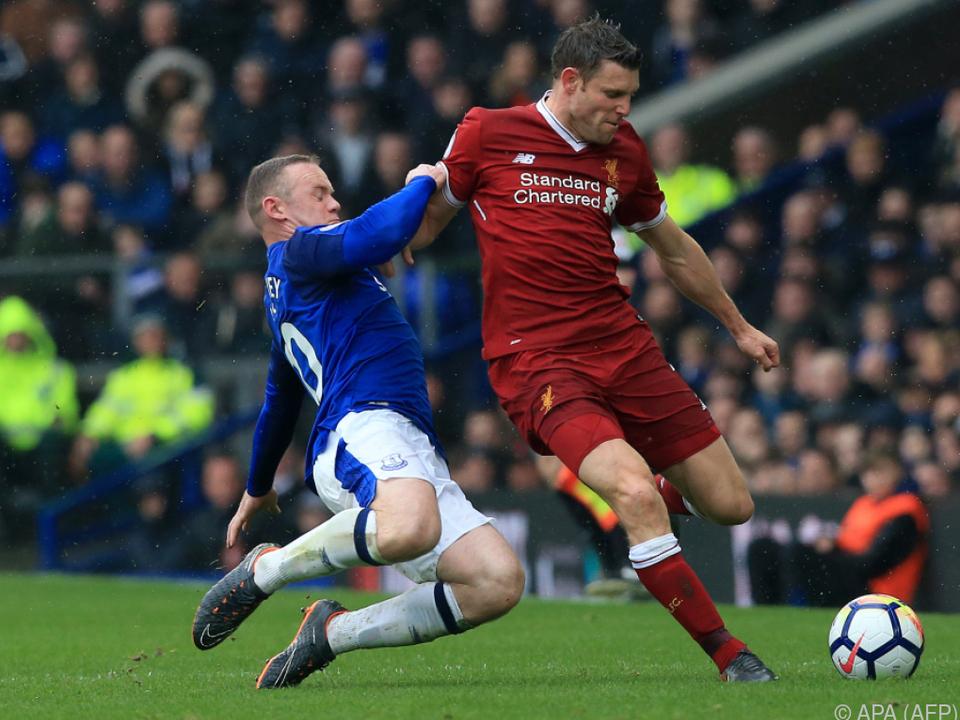 Everton\'s Wayne Rooney grätscht LFC-Spieler James Milner nieder