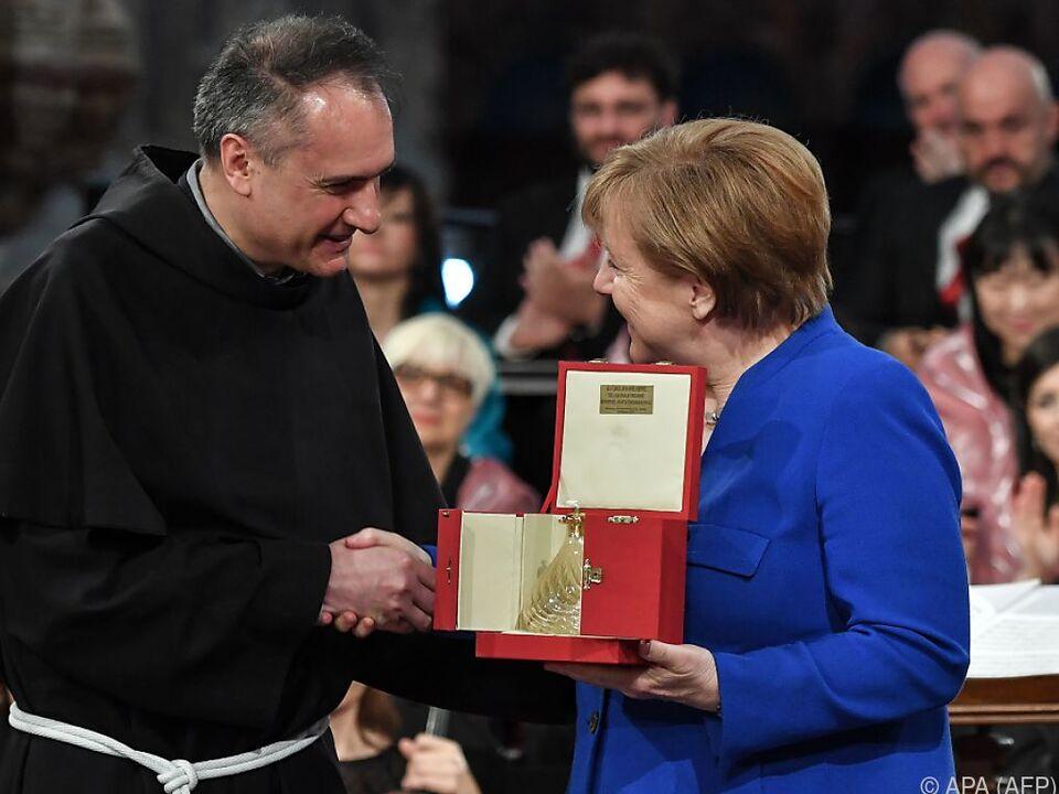 Merkel erhält Friedenslicht der Franziskaner für Friedensbemühungen