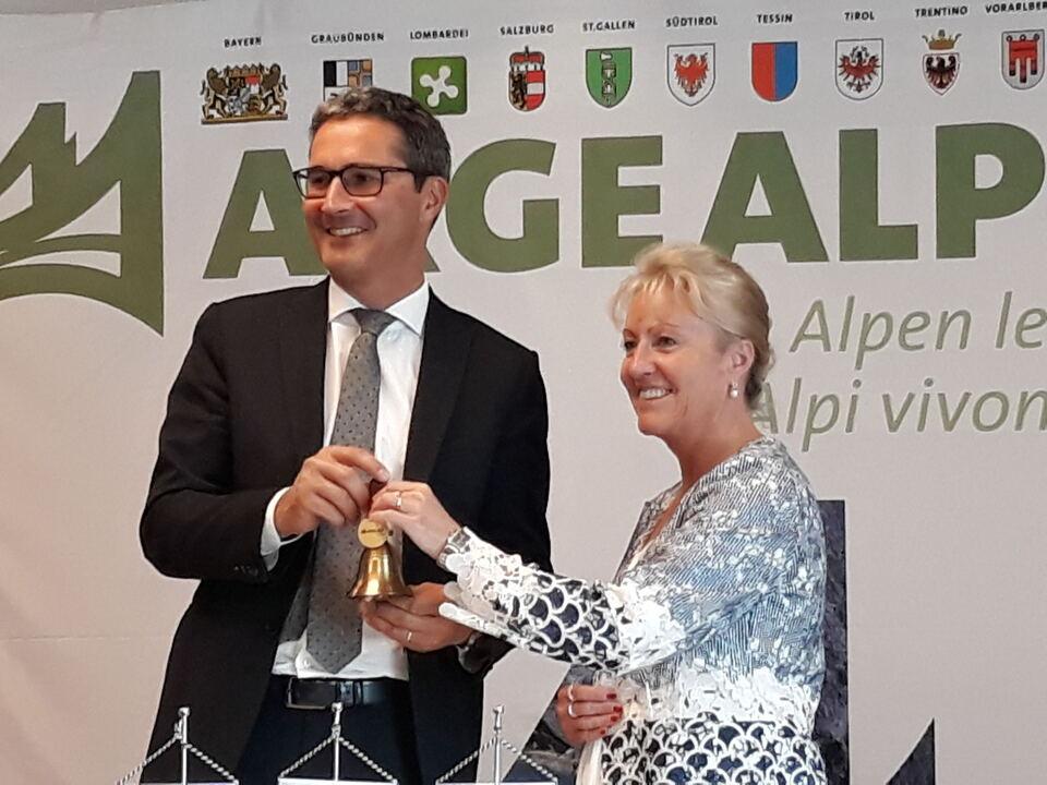 Kompatscher übernimmt das Arge-Alp-Glöcklein von der Bündner Regierungsrätin Barbara Janom Steiner