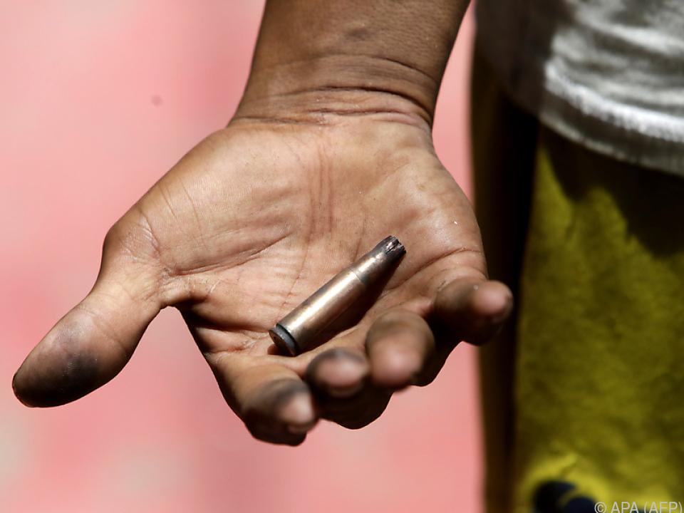 Ein Demonstrant zeigt die Kugel einer im Einsatz benutzten Waffe