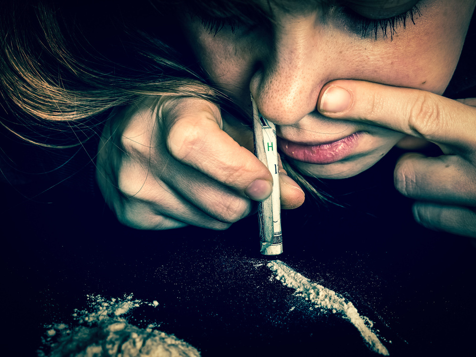 kokain drogen Junkie woman snorting cocaine powder with rolled banknote
