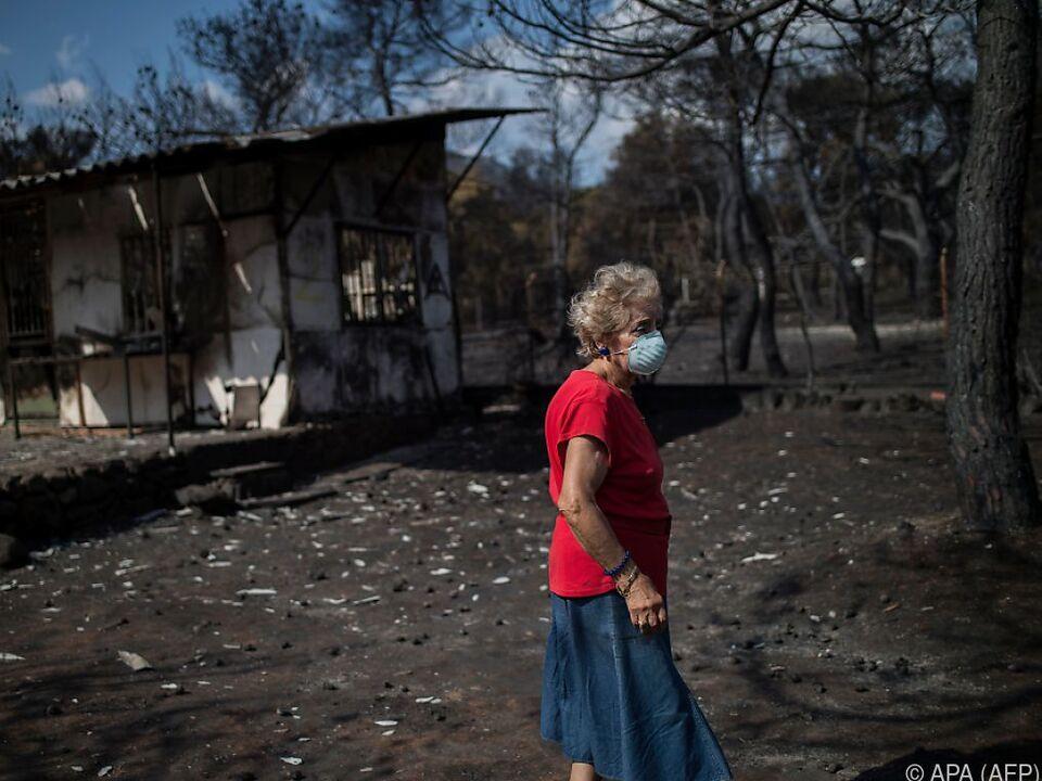 Frau zwischen den Trümmern nach der Brandkatastrophe