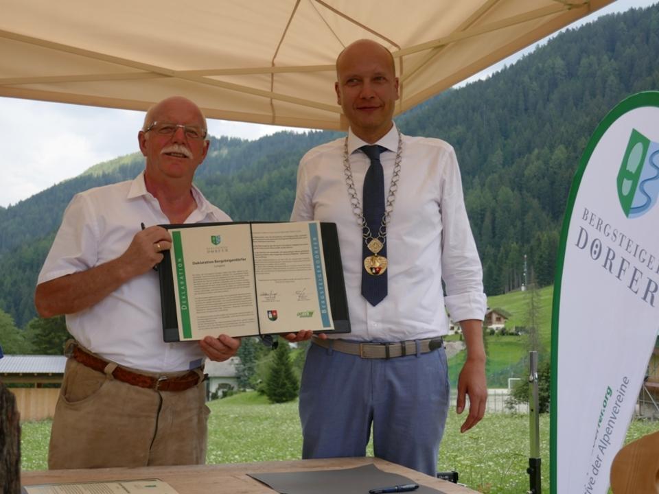 Im Bild (von links): AVS-Präsident Georg Simeoni, Bürgermeister Giorgio Costabiei mit der unterzeichneten Bergsteigerdorf-Deklaration Foto:
