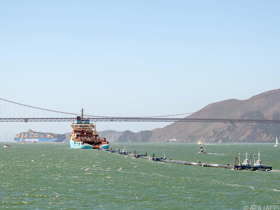Ein Schiff zieht die lange Konstruktion ins offene Meer