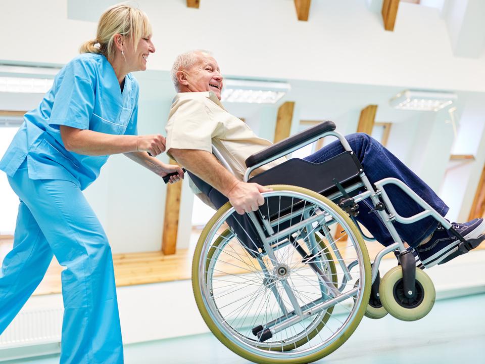 Krankenschwester Pflegekraft und Senior im Rollstuhl albern herum im Altenheim oder der Reha