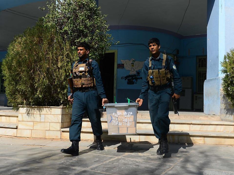 Kisten mit Stimmzettel werden von der Polizei abtransportiert