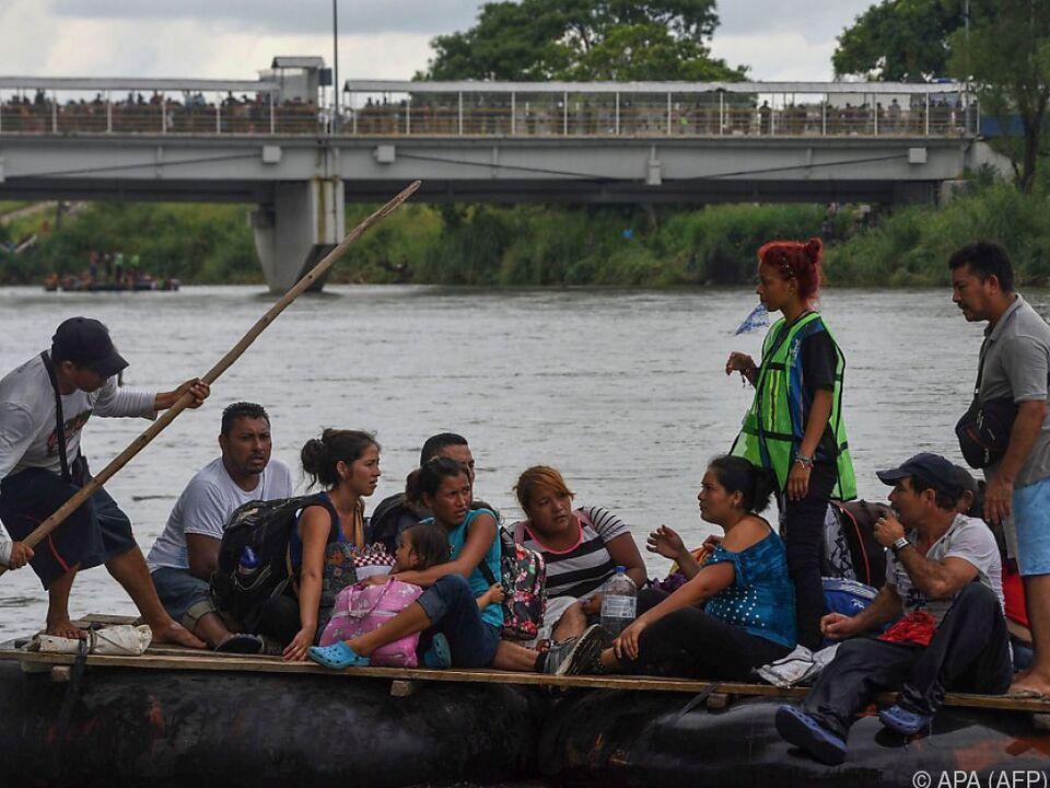 Migranten versuchen Überfahrt - dahinter die überfüllte Grenzbrücke