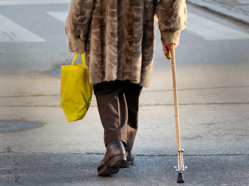 Eine ältere Frau mit einer Einkaufstasche und einem Gehstock. Invalidität Zivilinvalid