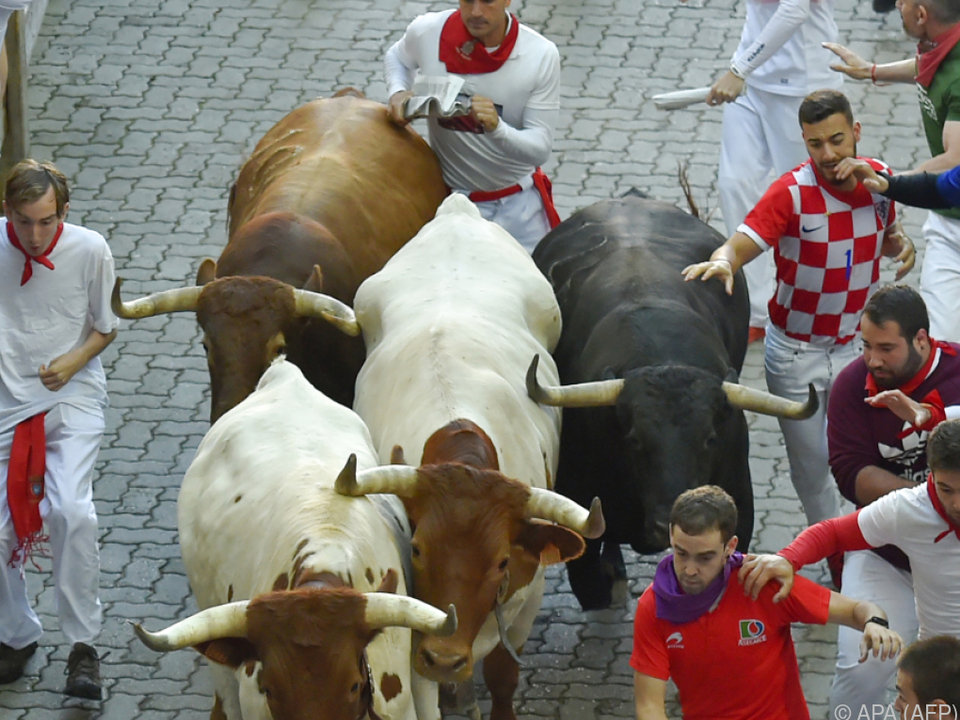 Teilnehmer rennen mit den Bullen in Pamplona