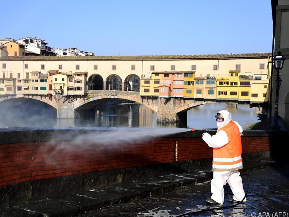 Auf dem Bild sieht man einen Arbeiter im Schutzanzug, der öffentliche Straßen reinigt.