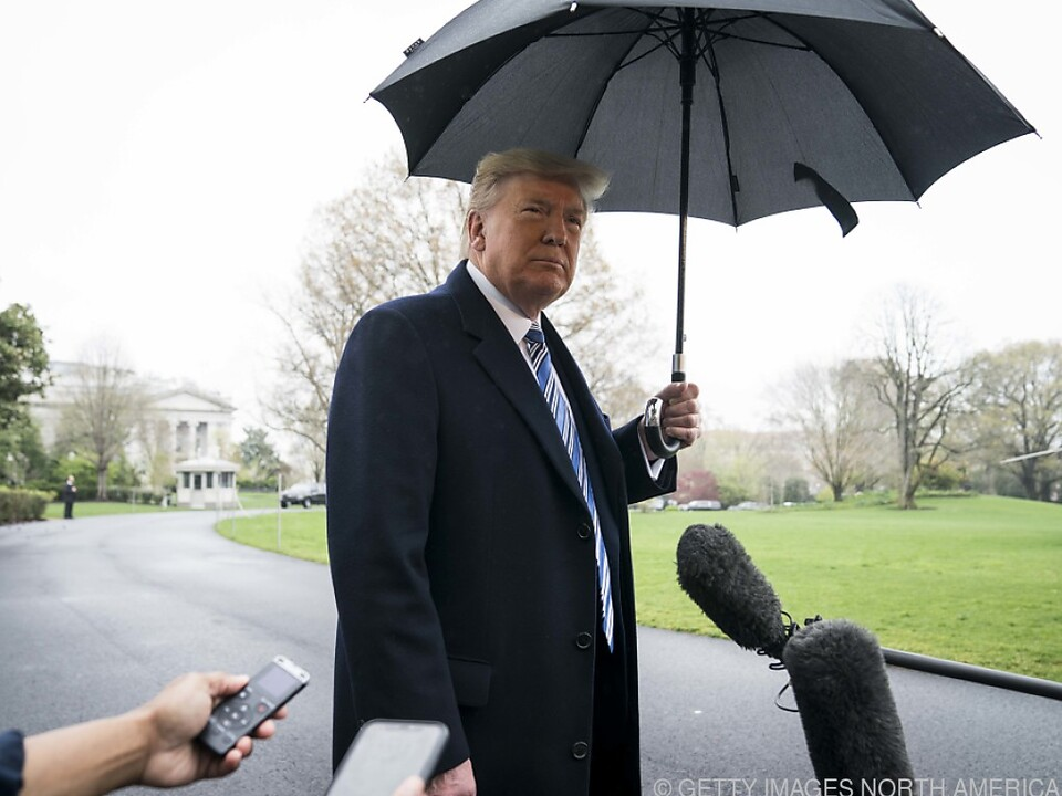 Donald Trump steht im Regen vor dem Weißen Haus