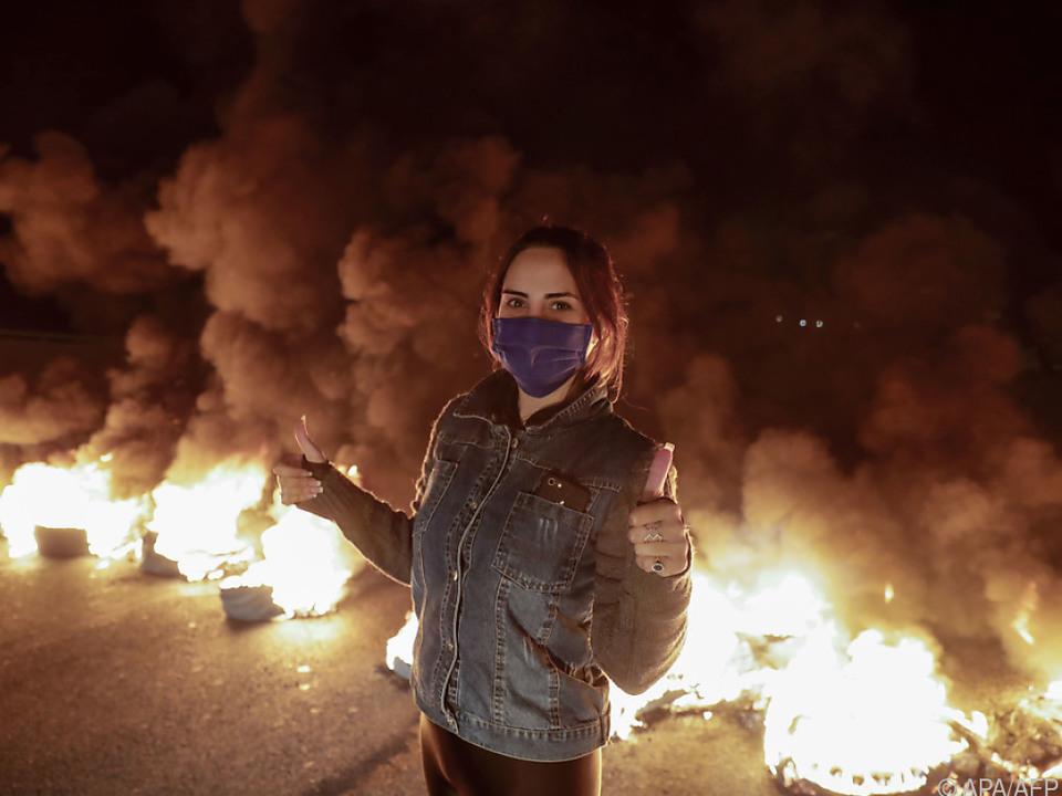 Straßensperre aus brennenden Reifen und Demonstrantin mit Mundschutz nördlich von Beirut