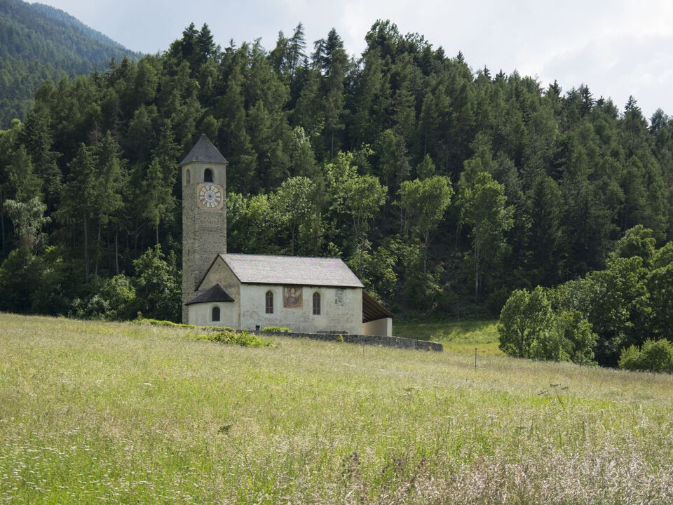 Die Kirche St. Johann mit dem ummauerten Friedhof liegt malerisch und weithin sichtbar in Waldnähe erhöht über Prad: Nun hat die Landesregierung einen Denkmalschutz für das Umfeld der Kirche beschlossen. (Foto: LPA/Udo Thoma)