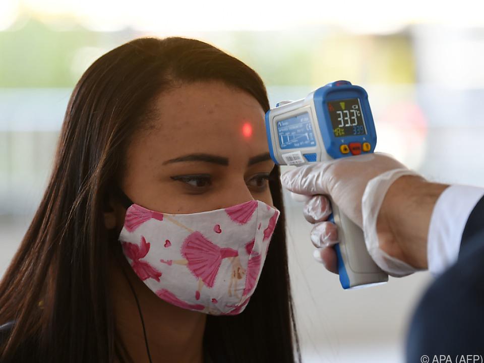 Bei einer Frau in Brasilia wird die Temperatur gemessen
