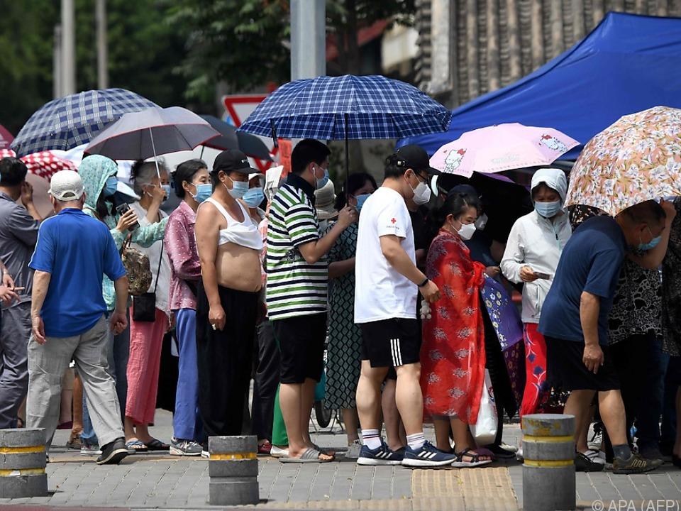Menschen stellen sich nach Besuch des Markts für Corona-Tests an