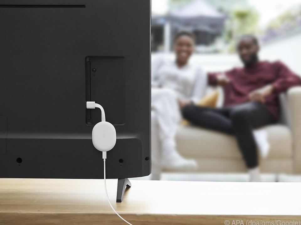 Das Chromecast-Gerät für TV-Streaming versteckt sich dezent hinter dem Fernseher