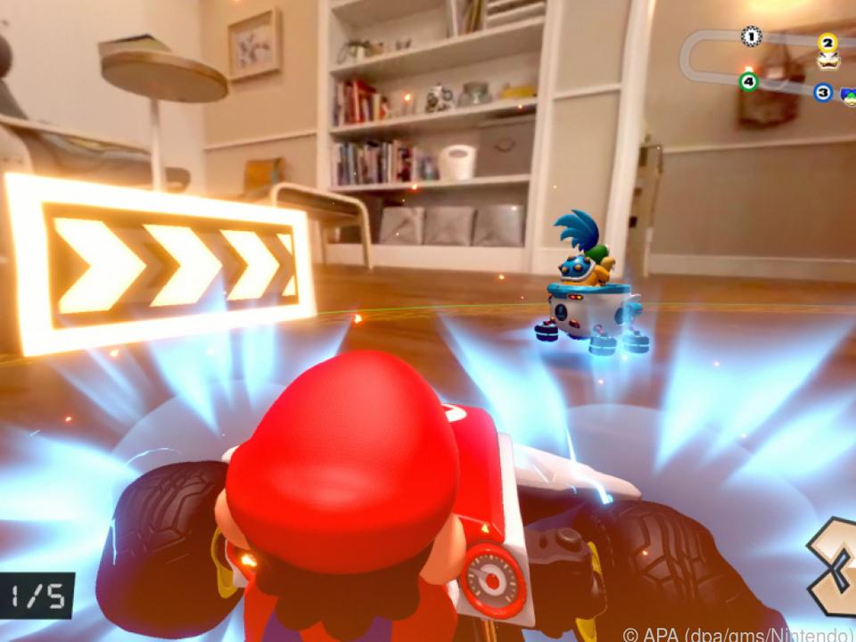 Der digitale Super-Mario rast im realen Spielzeug-Kart durch die Wohnung