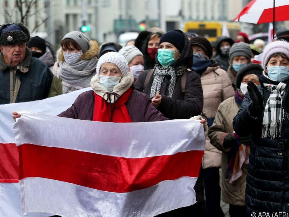 Demonstranten mit historischen weiß-rot-weißen Fahnen