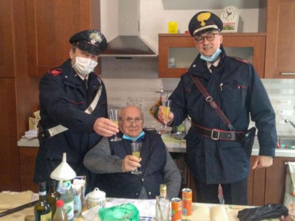 Fiorenzo Malvolti, 94 anni, brinda con due carabinieri della stazione di Alto Reno Terme, Bologna, 24 dicembre 2020.