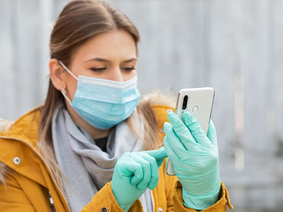 1095498_young-woman-with-mask-and-gloves-holding-smart-phone