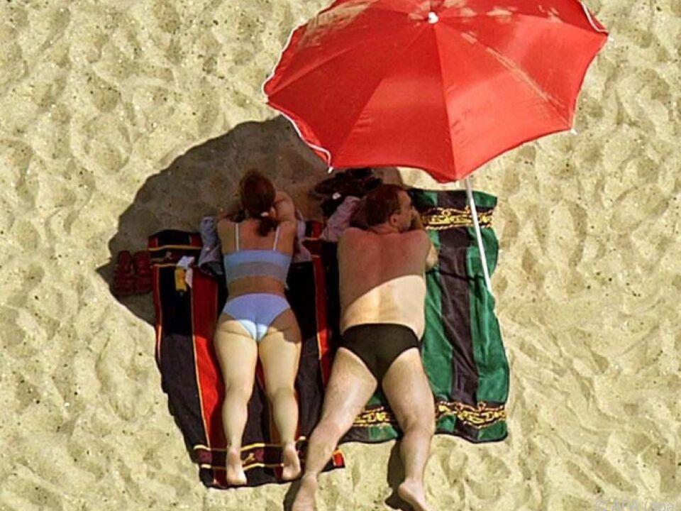 Ein Paar geniesst unter einem Sonnenschirm liegend den Sandstrand