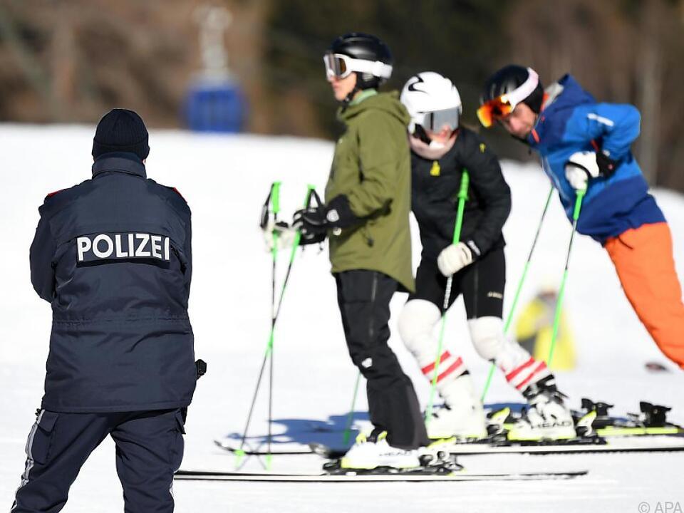 Polizei und Wintersportler auf einer Skipiste