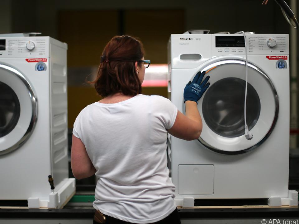 Eine Arbeiterin klebt Aufkleber auf eine Waschmaschine