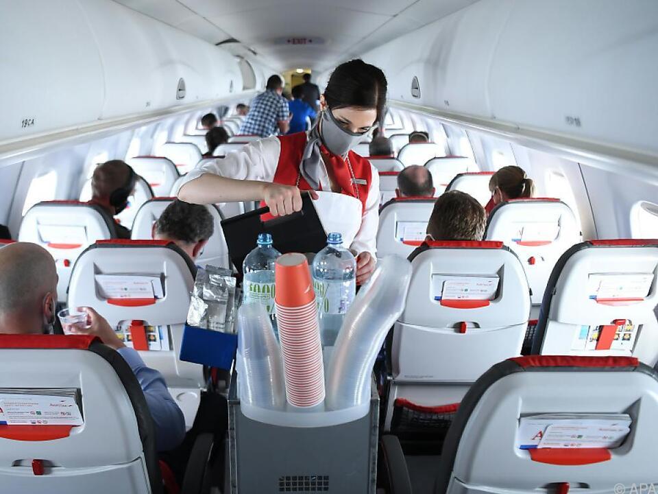 Eine AUA-Flugbegleiterin serviert Getränke