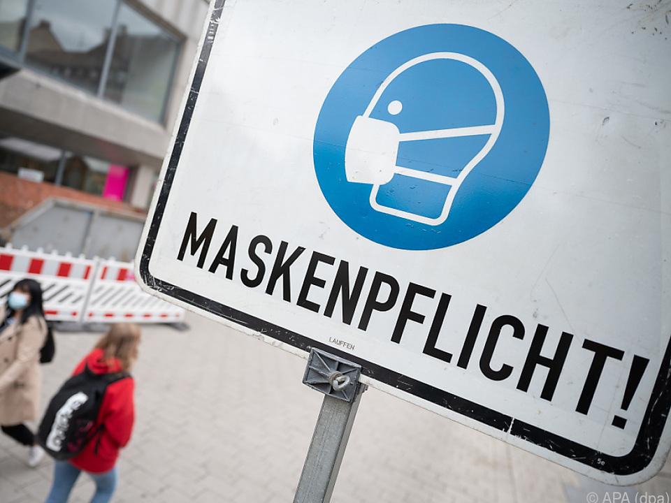 Straßenschild mit Maskenpflicht