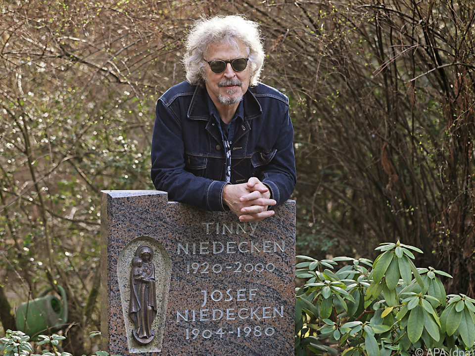 Wolfgang Niedecken lehnt am Grabstein seiner Eltern