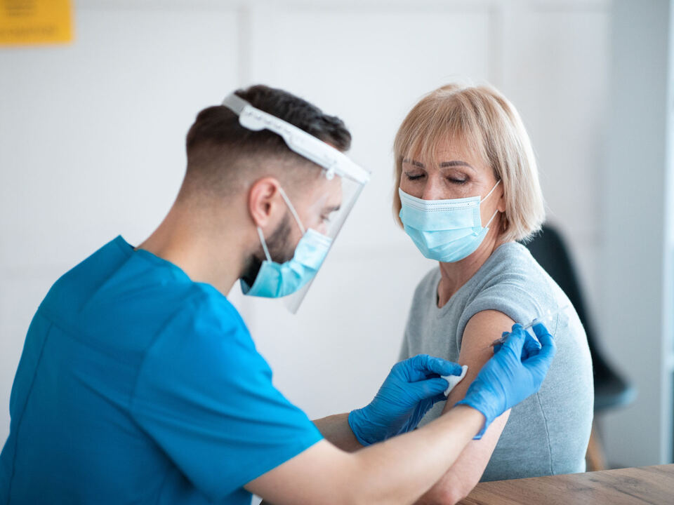Coronavirus prevention and treatment concept. Senior female patient getting vaccinated against covid-19 at clinic. Young medic making antiviral vaccine injection to mature woman, 1104643_162323192_l