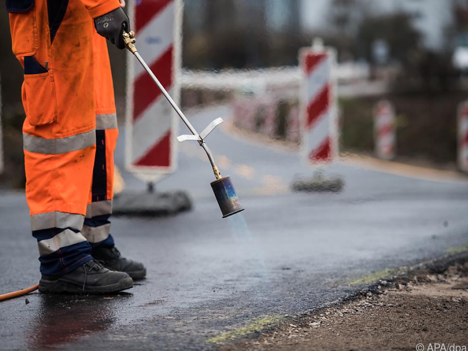 Ein Bauarbeiter arbeitet an einem neuen Straßenbelag