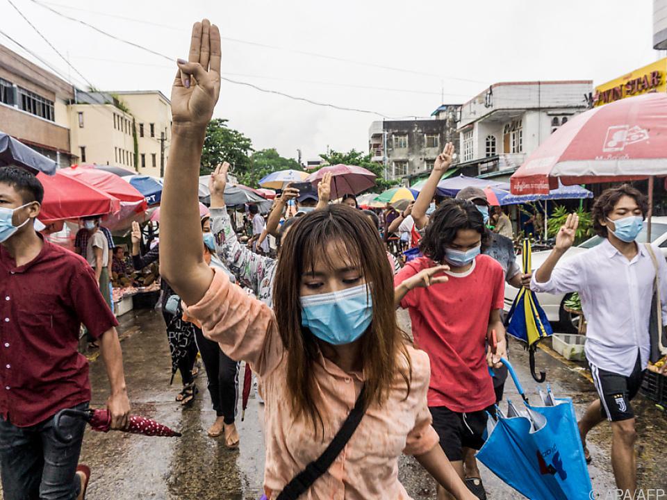 Demonstranten halten als Zeichen des Protests drei Finger in die Höhe