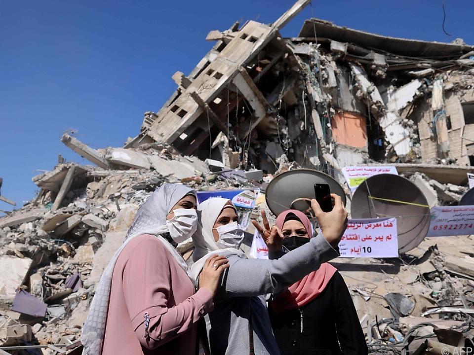 Drei Frauen fotografieren die Zerstörungen in Gaza City