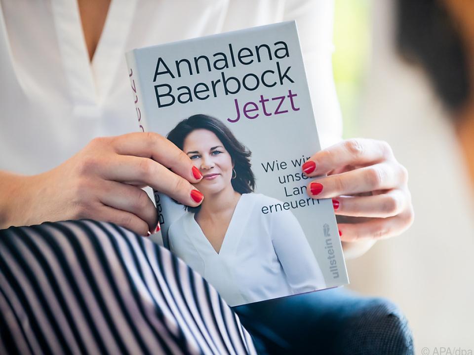 Baerbock hält ein Exemplar ihres Buches in Händen