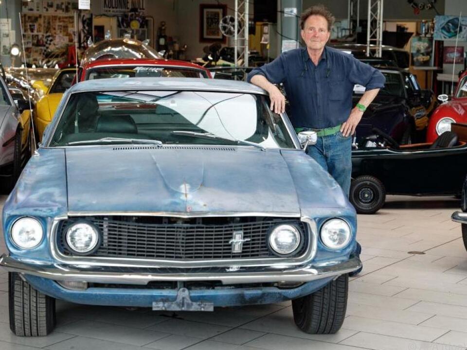 Oldtimerhändler Michael Fröhlich neben dem Ford Mustang